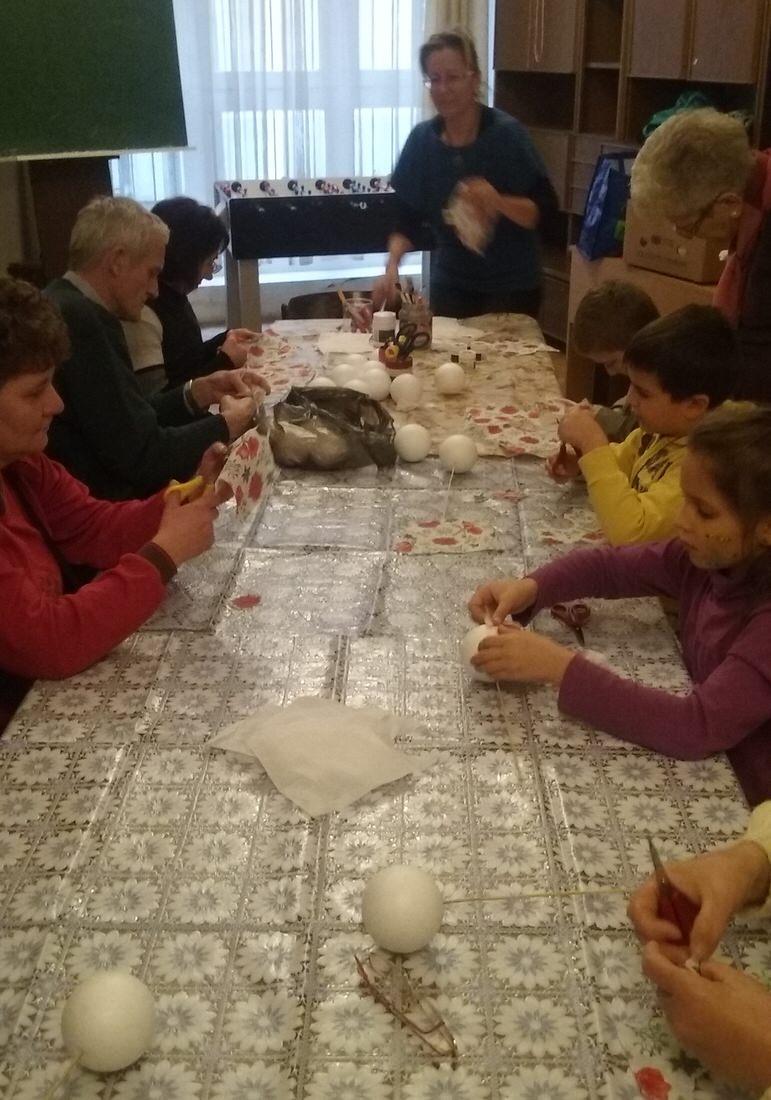 az asztal körül mindenki elkezdi készíteni a díszt